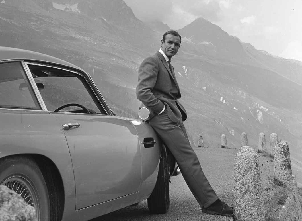 Sean Connery as James Bond leaning against an Aston Martin DB5 in the Alps